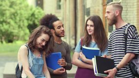 Footage of young students standing in front of university, talking. stock video footage