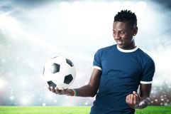 Footbal supporter with blue shirt and ball. With a stadium background Stock Photo