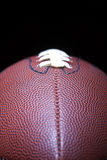 Football. Close up of an american football against a black background Royalty Free Stock Image