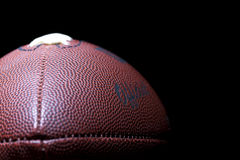 Football. Close up of an american football against a black background Stock Photography