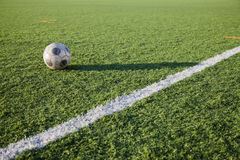 Football. Concept. An old ball in an artificial grass and corner lines of a field Stock Photos
