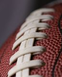 Football. Close up over dark grey with shallow depth of field and focus on second seam Stock Photos