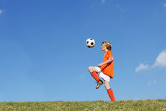 Football. Fit active boy child playing football or soccer kicking ball royalty free stock photography
