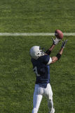 Football action photo of athlete catching a touchdown pass Royalty Free Stock Image