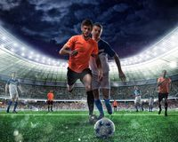 Football scene with competing football players at the stadium Royalty Free Stock Image