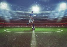Soccer player hits the ball from the midfield at the stadium Royalty Free Stock Images