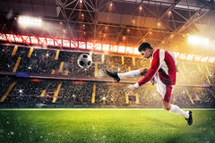 Football action in the stadium. Football player kicks the ball in the field of a stadium Royalty Free Stock Image