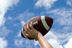 Football against Sky. Football in child's hand against blue sky with puffy clouds Stock Images