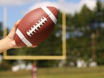 Football américain à disposition au-dessus de champ avec le poteau de but image stock