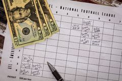 Football American office pool grid sports betting concept, flat lay. Football American office pool grid for sports betting concept with boxes, dollars, pen royalty free stock image