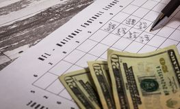Football American office pool grid for sports betting concept. With boxes, dollars, pen - partially completed grid. Friendly betting among co-workers, friends stock photography