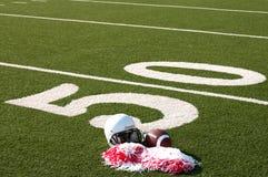 Football americano, casco e Pom Poms sul campo Fotografia Stock