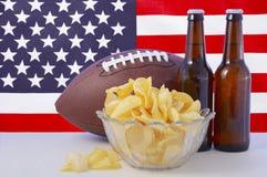 Football americano con birra e le patatine fritte Immagine Stock