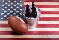 Football americano e birra ghiacciata sulla bandiera di legno rustica di U.S.A. immagini stock libere da diritti