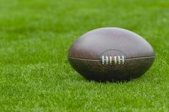 Football americano, palla di rugby sul fondo del campo di erba verde fotografia stock libera da diritti