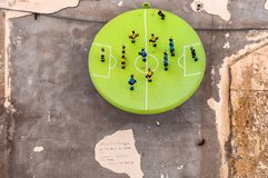 Football art installation in Syracuse - Italy. SYRACUSE, ITALY - AUGUST 17, 2014: art installation named La parabola del calcio by Alessandro Andolina on wall in Stock Photo