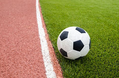 The football is on the artificial grass soccer field in the stadium Royalty Free Stock Photos