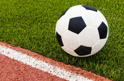 The football is on the artificial grass soccer field in the stadium. Royalty Free Stock Image
