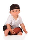 Football Baby. An adorable baby boy in a backwards cap holding his football. Isolated on white royalty free stock photos