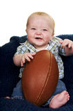 Football Baby. Smiling baby boy holding a big football Royalty Free Stock Images