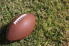 Football ball. A brown football ball lying in the grass of the lawn on the field Stock Photography