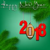 Football ball and 2018 on a Christmas tree branch. Happy New Year and numbers 2018 and football ball as a Christmas decorations hanging on a Christmas tree Royalty Free Stock Photography