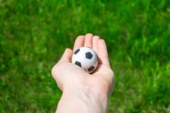 Football ball in female hand on background of green grass Royalty Free Stock Photos