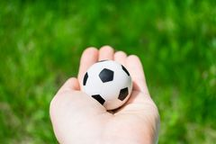 Football ball in female hand on background of green grass Stock Photo