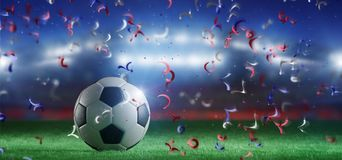 Football ball on the field of a world cup stadium with  streamer. View of a Football ball on the field of a world cup stadium with  streamers - 3d rendering Royalty Free Stock Images