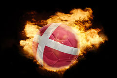 Football ball with the flag of denmark on fire. Football ball with the national flag of denmark on fire on a black background Stock Image