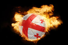 Football ball with the flag of georgia on fire. Football ball with the national flag of georgia on fire on a black background Stock Photo