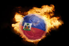 Football ball with the flag of haiti on fire. Football ball with the national flag of haiti on fire on a black background Royalty Free Stock Photos