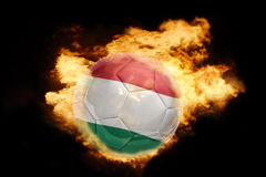 Football ball with the flag of hungary on fire. Football ball with the national flag of hungary on fire on a black background Royalty Free Stock Image