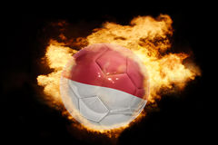 Football ball with the flag of indonesia on fire. Football ball with the national flag of indonesia on fire on a black background Royalty Free Stock Image