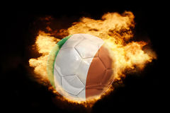 Football ball with the flag of ireland on fire. Football ball with the national flag of ireland on fire on a black background Stock Image