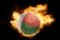 Football ball with the flag of madagascar on fire. Football ball with the national flag of madagascar on fire on a black background Stock Photography