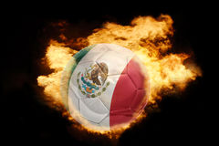 Football ball with the flag of mexico on fire. Football ball with the national flag of mexico on fire on a black background Stock Photos