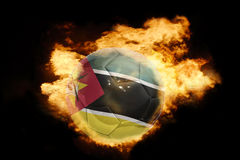 Football ball with the flag of mozambique on fire Stock Image