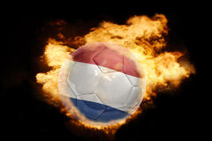 Football ball with the flag of netherlands on fire. Football ball with the national flag of netherlands on fire on a black background Royalty Free Stock Images