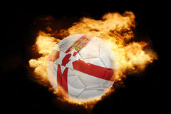 Football ball with the flag of northern ireland on fire. Football ball with the national flag of northern ireland on fire on a black background Stock Photos