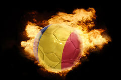 Football ball with the flag of romania on fire. Football ball with the national flag of romania on fire on a black background Royalty Free Stock Photography