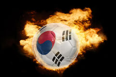 Football ball with the flag of south korea on fire. Football ball with the national flag of south korea on fire on a black background stock photos