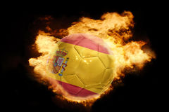 Football ball with the flag of spain on fire. Football ball with the national flag of spain on fire on a black background Stock Photo