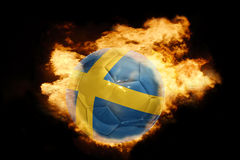 Football ball with the flag of sweden on fire. Football ball with the national flag of sweden on fire on a black background Stock Images