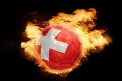 Football ball with the flag of switzerland on fire. Football ball with the national flag of switzerland on fire on a black background Royalty Free Stock Photo