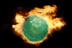 Football ball with the flag of turkmenistan on fire. Football ball with the national flag of turkmenistan on fire on a black background Royalty Free Stock Images