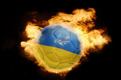 Football ball with the flag of ukraine on fire. Football ball with the national flag of ukraine on fire on a black background Royalty Free Stock Photo