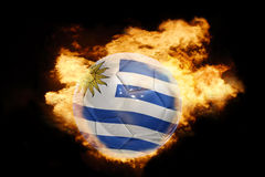 Football ball with the flag of uruguay on fire Royalty Free Stock Photos
