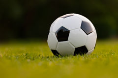 Football ball on green field Stock Photography