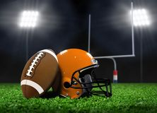 Football Ball and Helmet On Grass under Spotlights Stock Photo